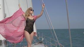 Une blonde dans des lunettes de soleil, un maillot de bain noir se tient sur un câble et pose sur un yacht flottant sur la mer et clips vidéos