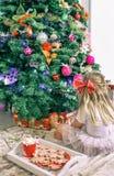 Une blonde de petite fille avec des arcs s'assied par l'arbre de Noël et la décore images libres de droits