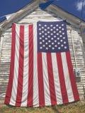 Une boîte aux lettres des États-Unis le long du côté d'une route de campagne en automne S Le drapeau voit accrocher sur un mur le image libre de droits