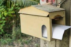 Une boîte aux lettres en bois de forme de maison accrochant sur un arbre Photo stock