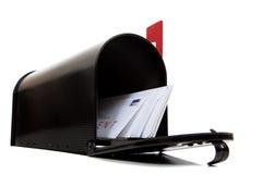 Une boîte aux lettres noire ouverte avec des lettres sur le blanc Photographie stock