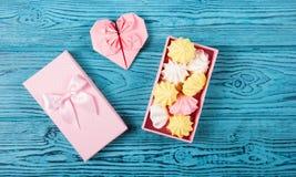 Une boîte avec des bonbons et un coeur de papier Meringues d'air dans un boîte-cadeau rose Image stock