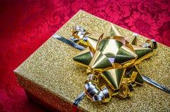 Une boîte de présent d'or avec l'arc sur le rouge photographie stock