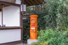 Une boîte rouge de courrier dans la vieille ville ou les vieux bâtiments de Magome de N image libre de droits