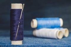 Une bobine des fils bleus avec une aiguille de couture sur le fond des bobines des fils bleus et blancs sur un tissu de denim photographie stock libre de droits