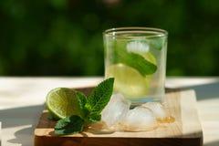 Une boisson fraîche de chaux et de menthe sur un conseil en bois Photo stock