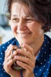 Une bonne femme d'une cinquantaine d'années élégante avec une tasse de café W de sourire image libre de droits