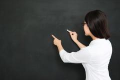 Une bonne question asiatique d'écriture de professeur sur le tableau noir avec la craie images stock