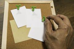 Une borne humaine droite de main sur le petit livre blanc vide sur le panneau de liège Image libre de droits