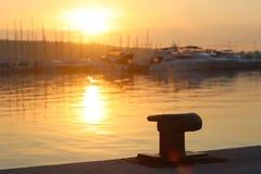 Une borne vide sur la marina dans la marina contre le contexte des yachts dans les rayons du Soleil Levant Éclairage orange Manqu photographie stock