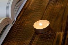 Une bougie brûlante se tient sur les planches en bois à côté d'un livre blanc ouvert de religion et de foi photos stock