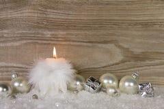 Une bougie brûlante avec les plumes blanches et le décor de neige et d'argent image libre de droits