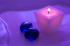 Une bougie brûlante rose avec les cailloux bleus en verre Bougie pour des salons de station thermale Tonalité pourpre images stock