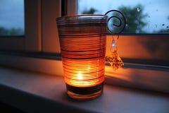 Une bougie brûle sur le rebord de fenêtre Image stock