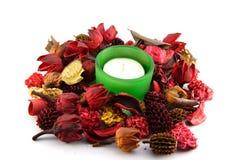 Une bougie dans coloré sèchent des lames et des fleurs Photos libres de droits