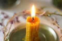 Une bougie de cire brûle avec une flamme chaude lumineuse photos libres de droits