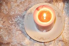 Une bougie rose blanche brûlante sur une soucoupe en porcelaine, se tenant sur un tissu argenté Photo stock