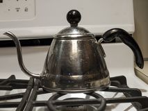 Une bouilloire de thé brillante sur un fourneau Image stock