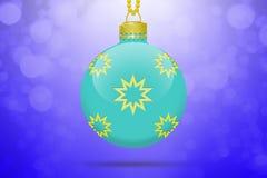 Une boule accrochante bleu-clair d'arbre de Noël avec les ornements d'or d'étoiles sur un fond bleu avec la fusée de lentille Photos stock
