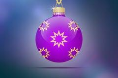 Une boule accrochante pourpre d'arbre de Noël avec les ornements d'or d'étoiles sur un fond bleu avec la fusée de lentille Photographie stock