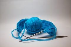 Une boule de fil bleu sur un fond blanc avec des aiguilles de tricotage photo libre de droits