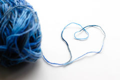 Une boule de fil de laine bleu Le fil a présenté la forme d'un coeur Photographie stock