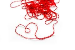 Une boule de fil de laine rouge Le fil a présenté la forme d'un coeur C Image stock