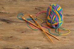 Une boule de laine avec des aiguilles de tricotage Photographie stock