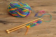 Une boule de laine avec des aiguilles de tricotage Image libre de droits