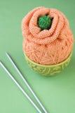 Une boule du fil pour tricoter une fleur sur un fond vert Photographie stock