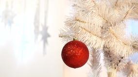 Une boule en verre rouge de décoration sur l'arbre de Noël banque de vidéos