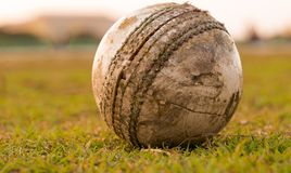 Une boule fortement utilisée pour jouer au cricket, se trouvant sur le terrain de jeu l'Inde photo stock