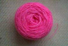 Une boule ronde de fil rose sur le fond blanc de la toile Images libres de droits
