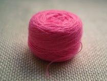Une boule ronde de fil rose sur le fond blanc de la toile Photo stock