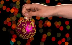 Une boule rose dans la main, sur un fond abstrait foncé Image stock