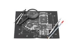 Une boussole, loupe et crayons au-dessus d'un dessin de construction o photos stock