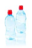 Deux bouteilles avec de l'eau sur le blanc Photos stock