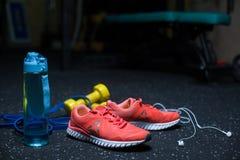 Une bouteille bleue, les espadrilles cramoisies, un téléphone portable avec des écouteurs, deux haltères jaunes sur une obscurité Image libre de droits
