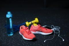 Une bouteille bleue, les espadrilles cramoisies, un téléphone portable avec des écouteurs, deux haltères jaunes sur une obscurité Images libres de droits