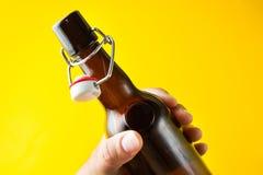Une bouteille brune avec de la bière sans label sur un fond jaune dans sa main images libres de droits