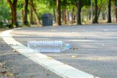 Une bouteille d'eau potable salissant sur un rez-de-chaussée de route au parc vert avec brouillé une poubelle dans le sideway photos libres de droits