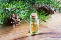 Une bouteille d'huile essentielle avec le sapin de Douglas s'embranche Photo stock