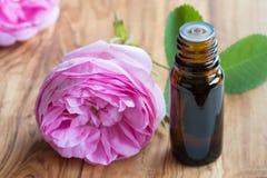 Une bouteille d'huile essentielle de rose avec les fleurs roses dans le backgrou Image stock
