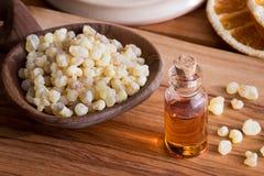 Une bouteille d'huile essentielle d'encens avec de la résine d'encens images libres de droits