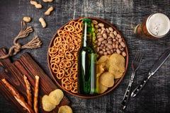Une bouteille de bière d'un plat avec les bretzels d'ookies, les pistaches et les pommes chips salés sur un panneau de craie rayé images stock