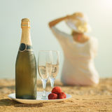 Une bouteille de champagne, de verres et de fraises sur le fond des femmes Photographie stock