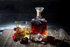 Une bouteille de cognac, de whiskey avec deux verres et de fruits sur le fond en bois Image libre de droits