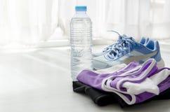 Une bouteille de l'eau, les chaussures de sport et le sportwear avec la fenêtre s'allument Images libres de droits