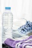 Une bouteille de l'eau, les chaussures de sport et le sportwear avec la fenêtre s'allument Photographie stock