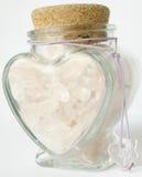 Une bouteille de quartz rose dans une bouteille en forme de coeur Photographie stock